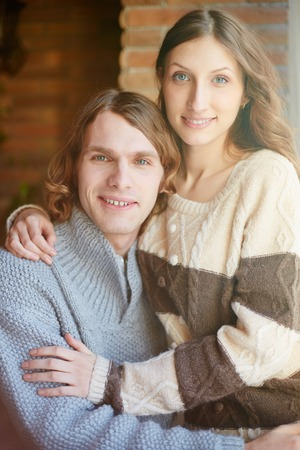 Portrait of sweethearts in sweaters embracing and looking at camera