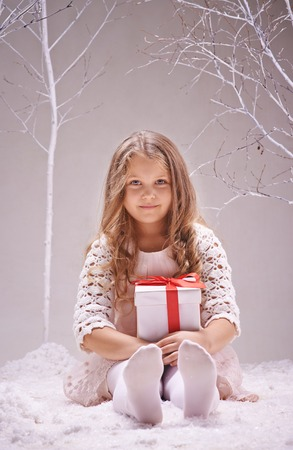 innocent: Adorable little girl with giftbox looking at camera