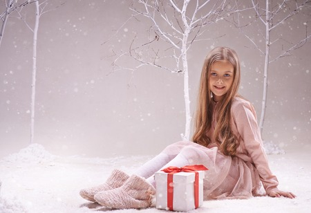 Happy adolescent girl with giftbox looking at camera while sitting in forest of wonders photo