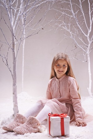 Happy adolescent girl with giftbox near by sitting and looking at camera photo