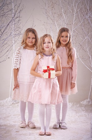 Cute adolescent girl holding giftbox with her two friends near by photo