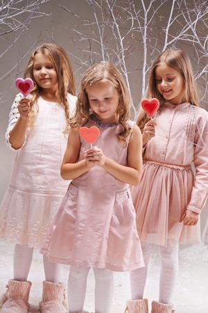 Three amazed girls with candy hearts in charmed winter forest photo