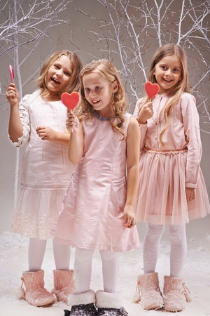 Group of ecstatic girls with candy hearts having fun in fairy garden photo