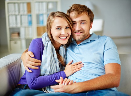 Amorous man and woman in casual having rest at home photo