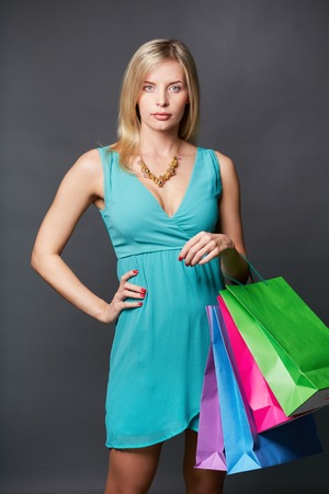 shopaholism: Portrait of calm woman with multi-color paperbags over grey background