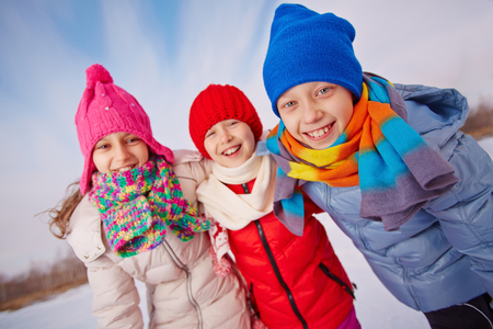 brothers and sisters: Happy little friends in winterwear looking at camera outside Stock Photo