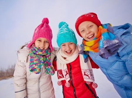 Group of ecstatic children in winterwear having fun outside photo