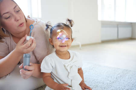 Little girl looking at soap bubbles blown by her mother photo