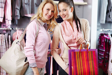 Two friendly females with shopping bags in department store photo