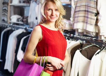 Portrait of beautiful shopper in red dress looking at camera in clothing department photo