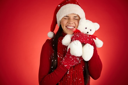 Cheerful girl in Santa cap expressing affection to white teddy bear photo