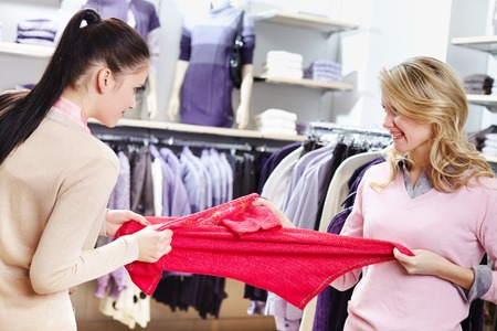 disinclination: Aggressive girls fighting for red tanktop in department store Stock Photo