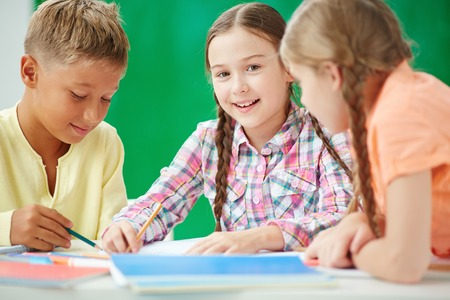 focus group: Cute learner looking at camera at lesson of drawing with her classmates near by