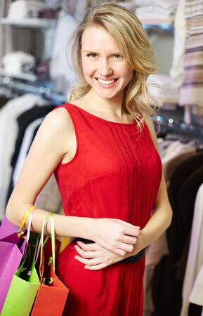 Portrait of smiling woman with paperbags looking at camera after shopping in clothing department photo