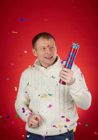petard: Joyful man in white knitted sweater holding confetti cracker