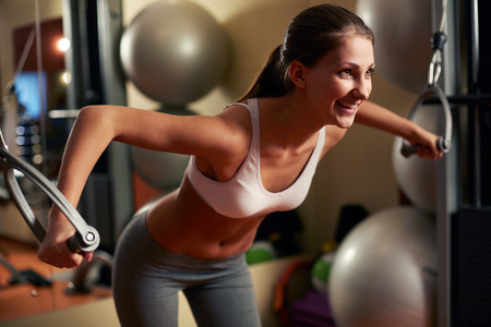 Young woman lifting weights at home gym Stock Photo