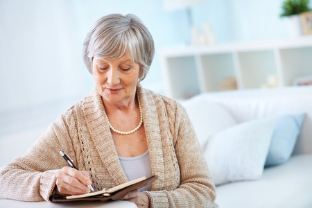 personas sentadas: Mujer mayor que hace notas en el bloc de notas Foto de archivo