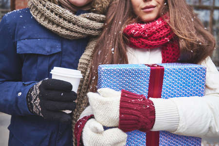 Close-up of girl with giftbox and her boyfriend with plastic glass of coffee outdoors photo