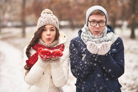 winterwear: Portrait of cute young dates in casual winterwear blowing snowflakes from palms