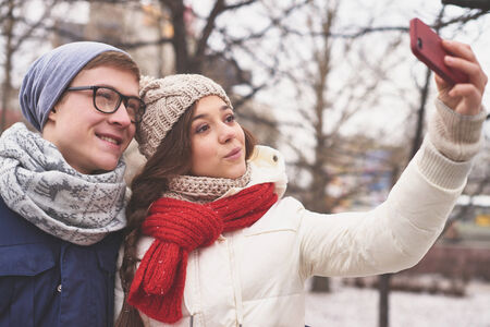 winterwear: Affectionate young dates in casual winterwear taking photo of themselves outdoors