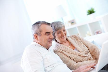 노트북을 사용하는 노인 부부