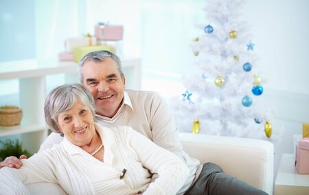 confortable: Senior couple sitting at Christmas tree at home Stock Photo