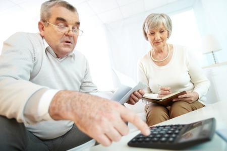 old man sitting: Senior couple making calculations