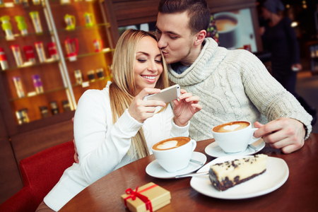 Young couple sitting in café and watching photos photo