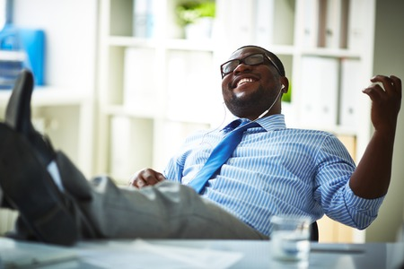 young executive: Office worker listening to music at workplace