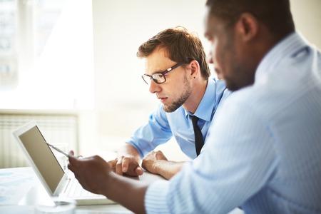 ノート パソコンに何かを議論するマネージャー