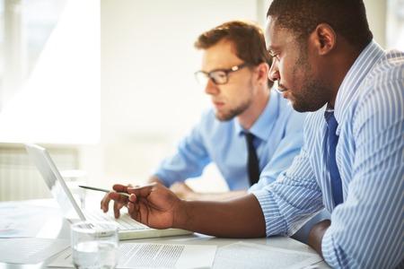 gerente: Hombre que señala en la computadora portátil de su colega Foto de archivo