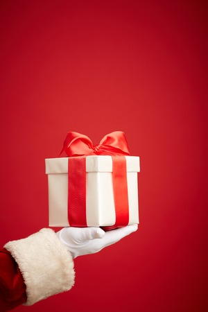 giftbox: Santa Claus gloved hand holding giftbox with red bow