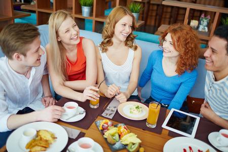 amigas conversando: Los jóvenes que se comunican en la cafetería