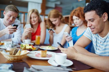 grupo de personas: Amigos que se sientan en la cafeter�a absortos en sus tel�fonos