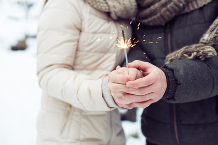 Close-up of Bengal light in hands of lovers photo