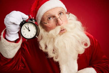 natale: Pensive Santa with alarm clock showing five minutes to xmas by his ear