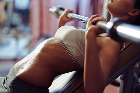 sudando: Mujer que levanta pesas en el gimnasio
