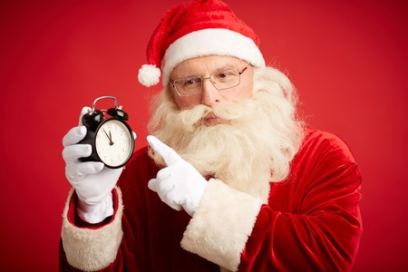 natale: Pensive Santa Claus with alarm clock pointing at it