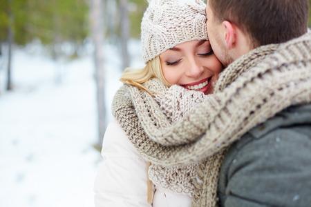 novios besandose: Mujer que abraza a su novio en invierno