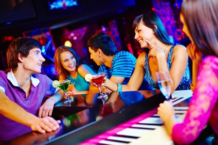Young people drinking and talking at nightclub photo