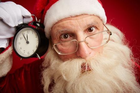 natale: Puzzled Santa holding clock showing five minutes to xmas and looking at camera
