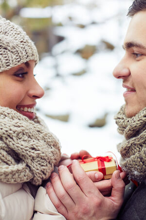 amorous woman: Young amorous couple with small present looking at one another outdoors