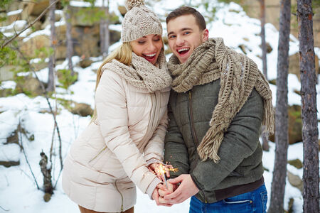 amorous woman: Happy couple with Bengal light celebrating holiday in winter forest