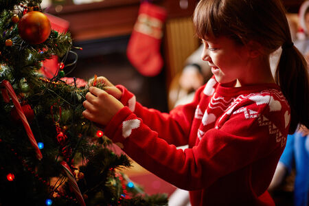 Little girl decorating Christmas tree with toys Stock Photo