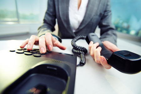 telephony: Businesswoman holding phone receiver and dialing number