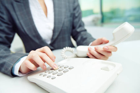 dialing: Businesswoman dialing telephone number Stock Photo