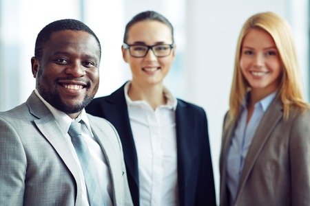 boss and employee: Smiling and confident businessman with two female colleagues on background