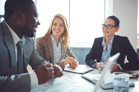 reuniones empresariales: Empresarias felices escuchando hombre joven explicaciones