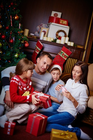 Happy family looking through gifts on Christmas evening at home photo