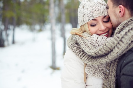winter couple: Young female in winterwear with her boyfriend near by